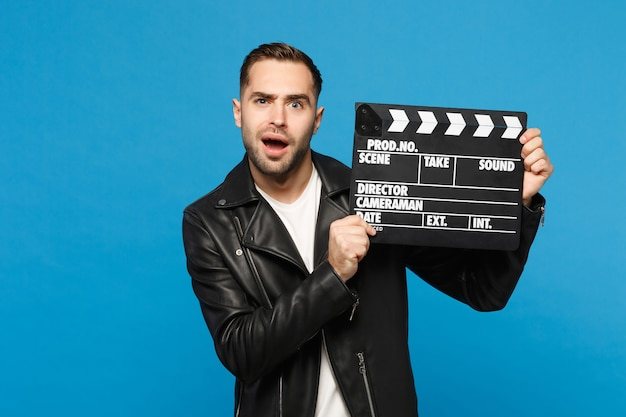 Perplexed stylish young unshaven man in black jacket white t-shirt hold in hand film making clapperboard isolated on blue wall background studio portrait. people lifestyle concept. mock up copy space.