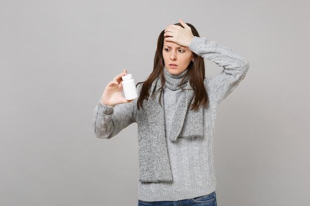Озадаченная женщина в сером свитере, шарфе положила руку на голову, удерживайте таблетки аспирина в бутылке, изолированной на сером фоне. здоровый образ жизни, лечение больных, концепция холодного сезона.