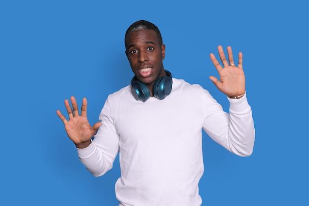 흰색 거리 착용 스웨터에 당황한 젊은 아프리카 계 미국인 남자가 파란색 배경에 고립 된 포즈, 손을 위로, 손바닥을 보여주는