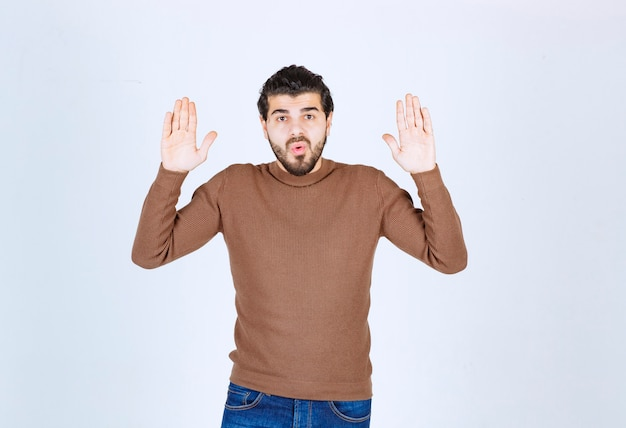 Perplexed young man guy in brown sweater posing with rising hands up. high quality photo