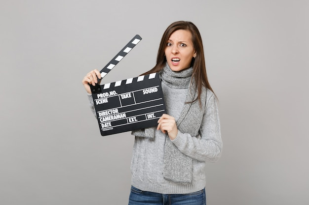 Perplexed young woman in gray sweater, scarf hold classic black film making clapperboard isolated on grey background. healthy fashion lifestyle people emotions cold season concept. mock up copy space.