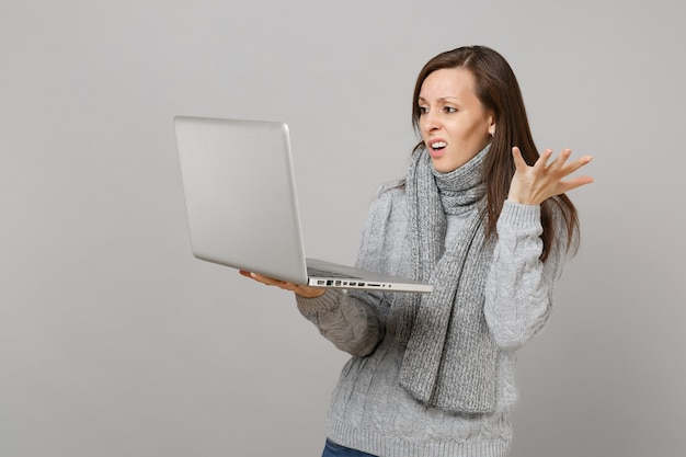 灰色のセーターとスカーフの手を広げて、灰色の壁の背景に分離されたラップトップpcコンピューターで作業している困惑した若い女性。健康的なライフスタイル、オンライン治療コンサルティング、寒い季節のコンセプト。