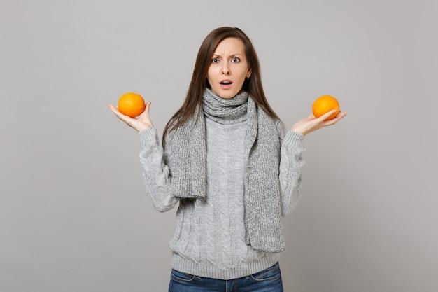 Озадаченная молодая женщина в сером свитере, шарфе, держащем апельсины, изолированные на сером фоне, студийный портрет. здоровый образ жизни моды, искренние эмоции людей, концепция холодного сезона. копируйте пространство для копирования.
