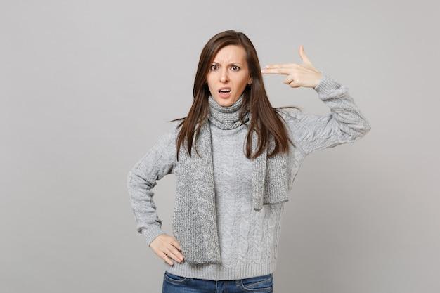 灰色のセーターを着た困惑した若い女性、スカーフは彼女が灰色の背景に孤立して自分自身を撃つように頭に指を向けます。健康的なファッションライフスタイル、人々の誠実な感情、寒い季節のコンセプト。