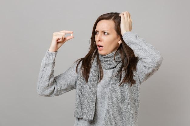회색 스웨터를 입은 어리둥절한 젊은 여성, 스카프가 머리에 손을 얹고 약물 태블릿, 회색 배경에 격리된 아스피린 알약. 건강한 생활 방식 아픈 질병 치료 추운 계절 개념.