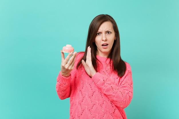 Озадаченная молодая женщина в вязаном розовом свитере, показывающем стоп-жест с ладонью, чтобы торт в руке, изолированной на синем бирюзовом стенном фоне, студийный портрет. концепция образа жизни людей. копируйте пространство для копирования.