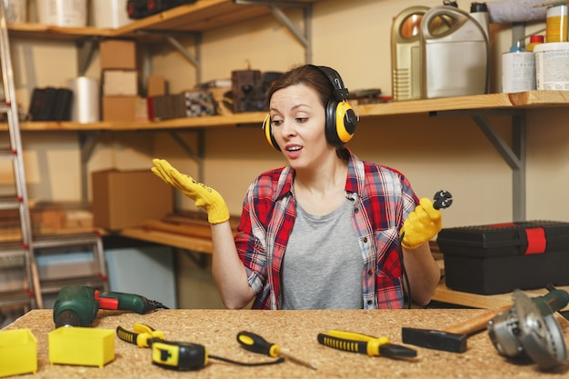 格子縞のシャツの灰色のtシャツノイズ絶縁ヘッドフォン黄色の手袋で困惑した若い女性は、木片、さまざまなツール、電動ドリル、ワイヤーで木製のテーブルの場所で大工のワークショップで働いています。