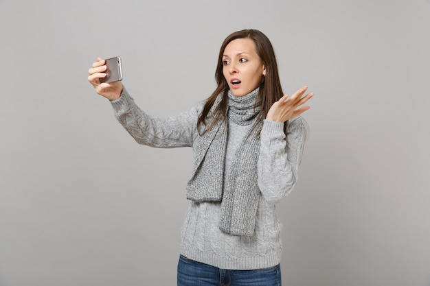 Perplexed young woman in sweater, scarf spreading hands, doing selfie shot on mobile phone making video call isolated on grey background. healthy fashion lifestyle people emotions cold season concept.