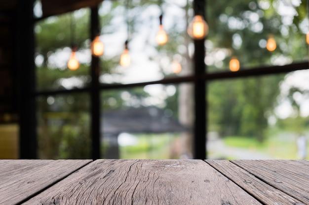 Persentationオブジェクトのためのぼんやりしたrestaurentの背景の前に古い木製のテーブル