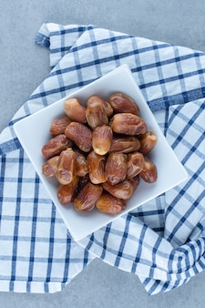 Persian dates in the bowl, on the tea towel, on the marble table.