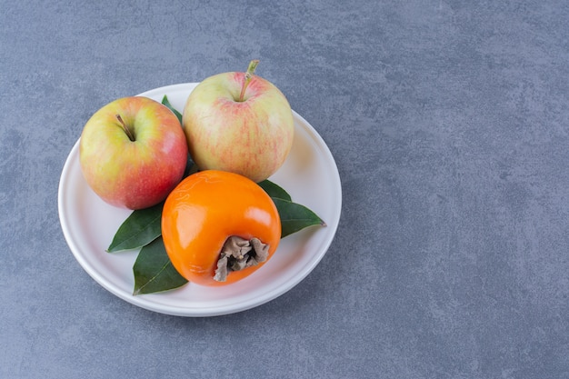 Хурма и яблоки на тарелке на мраморном столе.