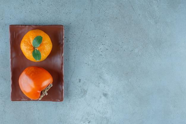 Хурма и апельсин на деревянной тарелке, на мраморном фоне. фото высокого качества
