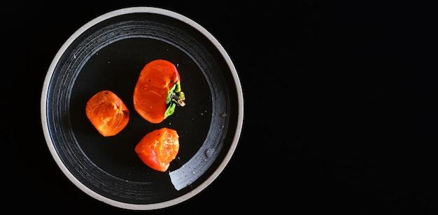 黒いプレート上の柿と柿のスライス、平らな暗い背景。上から見る