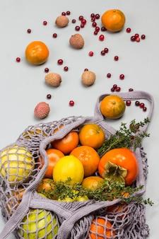 再利用可能なメッシュバッグに入った柿、リンゴ、レモン。テーブルの上のライチ、クランベリー、みかん。灰色の背景。上面図
