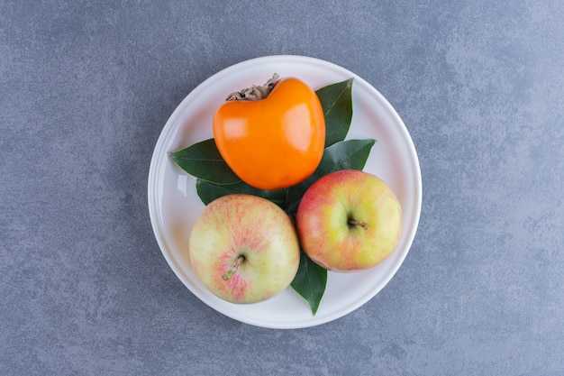 Persimmon and apples on plate on the dark surface