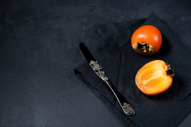 Persimmon on black fabric with copyspace.