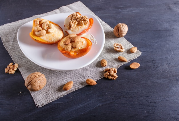 Persimmon dessert with curd, nuts and milk cream on black wooden surface.
