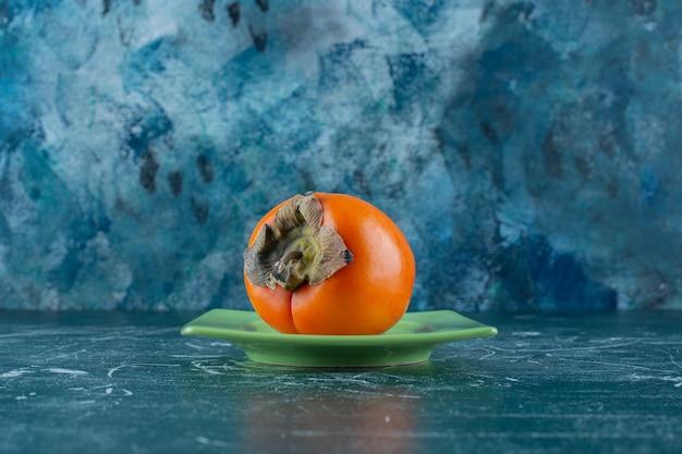 Плоды хурмы на подставке, на мраморном столе.
