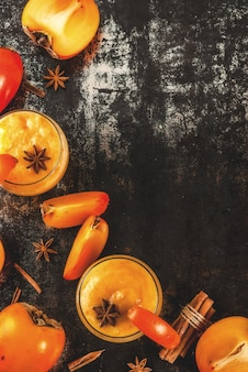Persimmon fruit smoothie with cinnamon and anise stars, dark rusty background copy space top view