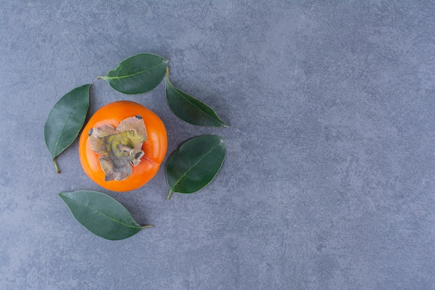 Persimmon fruits and leaves, on the dark surface