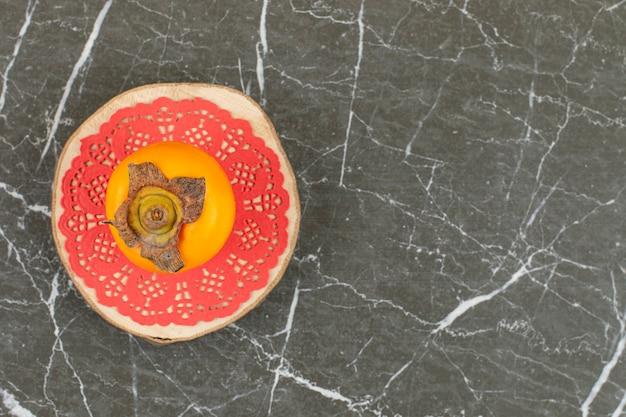 Хурма на розовой салфетке над деревянной тарелкой.
