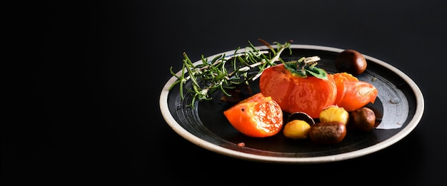 Persimmon and persimmon slices, rosemary branch on a black plate, selective focus