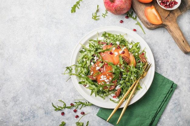 Persimmon salad with arugula, nuts, goat cheese, pomegranate. healthy vegetarian food concept.