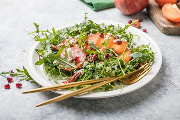 Persimmon salad with arugula, nuts, goat cheese, pomegranate. healthy vegetarian food salad concept.
