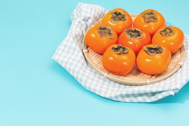 Persimmons on the blue background