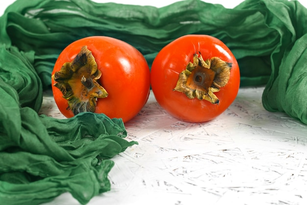 Persimmons on a napkin on a white background