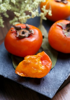 Persimmons on stone board