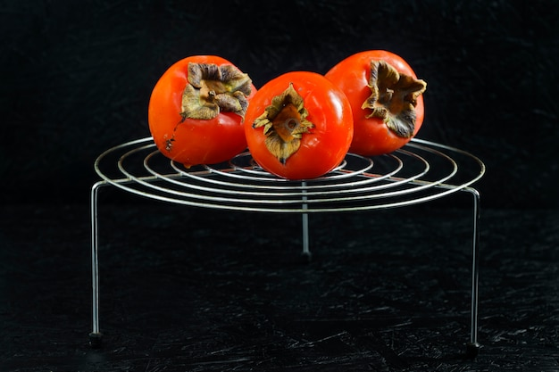 Persimmons on a trellised stand on a black background