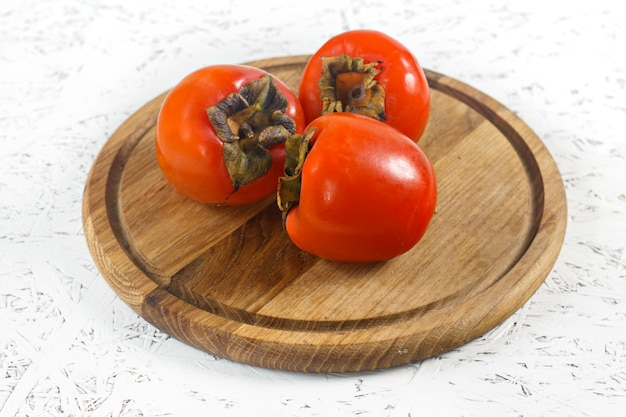 Persimmons on a wooden board on a white background