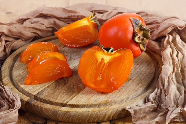 Persimmons on a wooden board on a wooden background