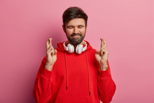 Persistant handsome bearded man stands with crossed fingers, closes eyes and waits for special moment, wears red sweatshirt and stereo headphones around neck, waits results, poses indoor alone