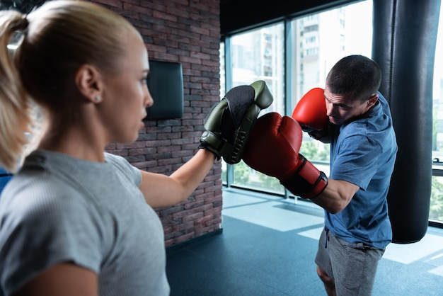 Persistent man. persistent athletic man boxing hard in gym with city view along with his female trainer