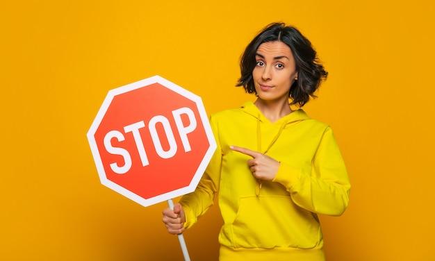 永続的な要件。黄色いパーカーを着た自信に満ちた粘り強い少女は、指で「一時停止」の標識を真剣に指しています。