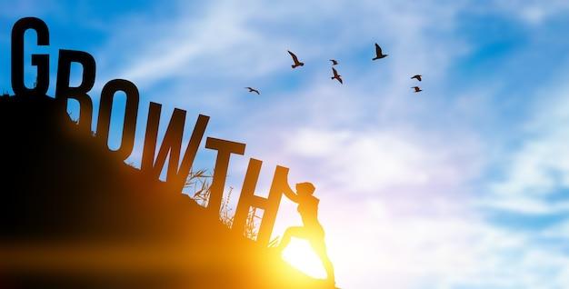 Концепция роста человека и бизнеса. силуэт человека, толкающего слово на вершине горы. успех в бизнесе и мотивация фото