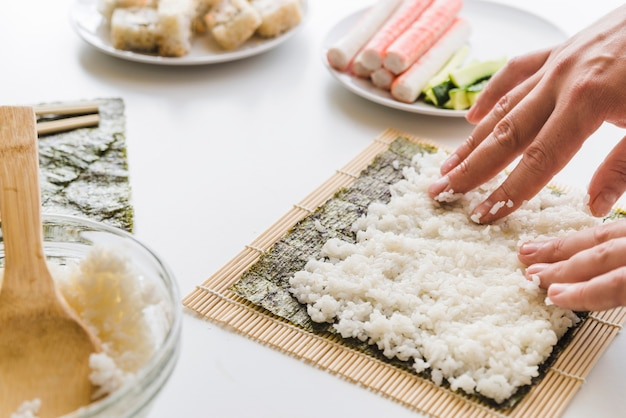 Person arranging rice layer