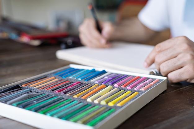 사람, 종이의 흰 시트에 파스텔 크레용 분필로 그림을 그리는 예술가와 나무 테이블에 pellette