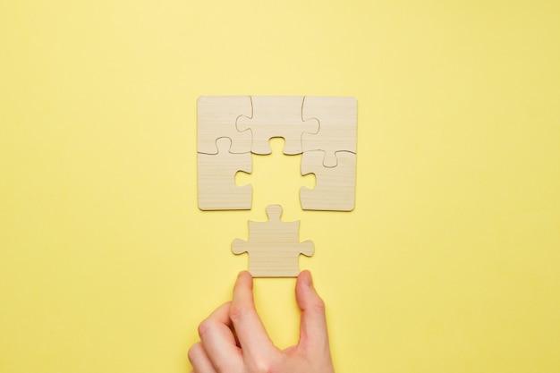 人は木製のパズルを組み立てて、最後のピースを接続します。
