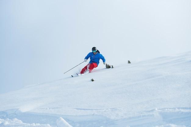 겨울에 알프스에서 스키를 타는 사람