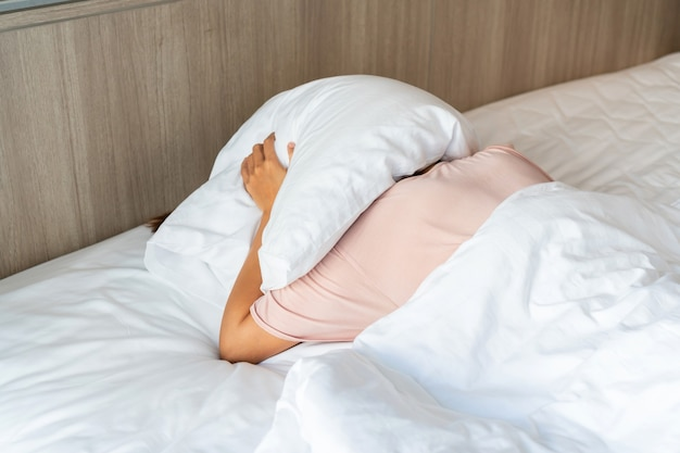 Person in bed using a pillow to cover her head to hide from the sunlight
