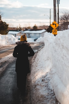 Person in black coat standing on snow covered road during daytime