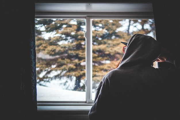 Person in black hoodie standing near window