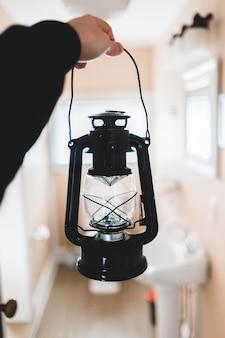 Person in black long-sleeved shirt holding black lantern