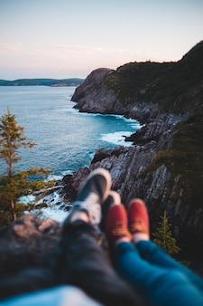 Persona in jeans blu denim seduto sulla scogliera sul mare durante il giorno