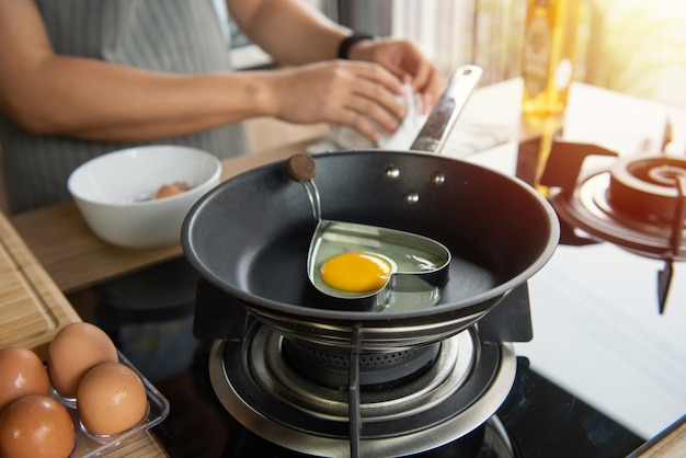 Person breaking an egg into heart mold in a pan