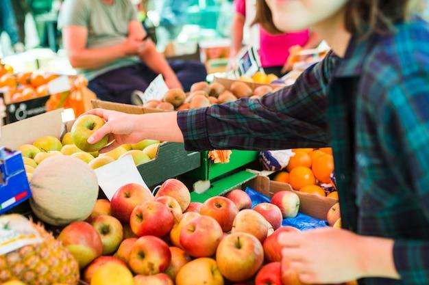 Человек, покупающий фрукты и овощи