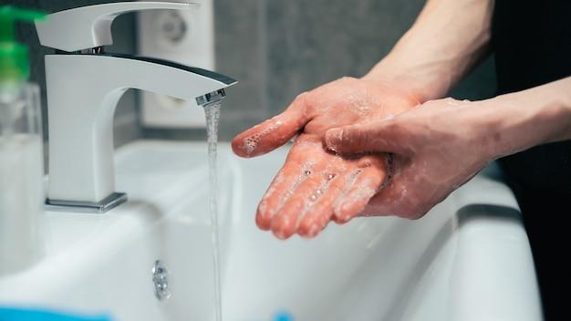 손바닥을 조심스럽게 비누 칠하는 사람